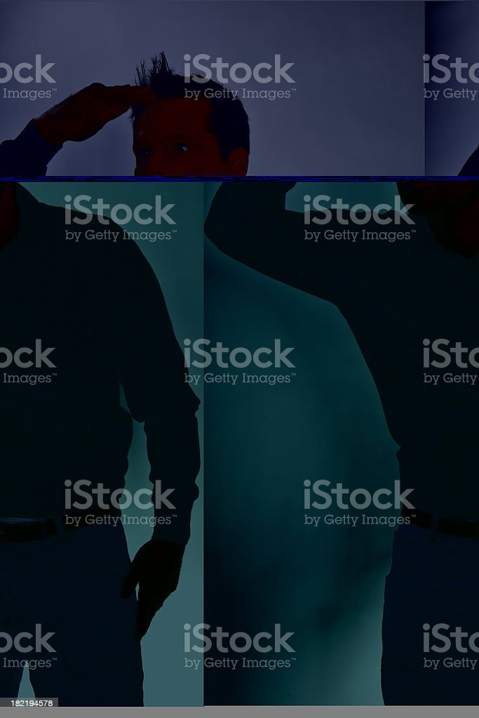 Portrait of  young man looking out somewhere shielding his eyes royalty-free stock photo