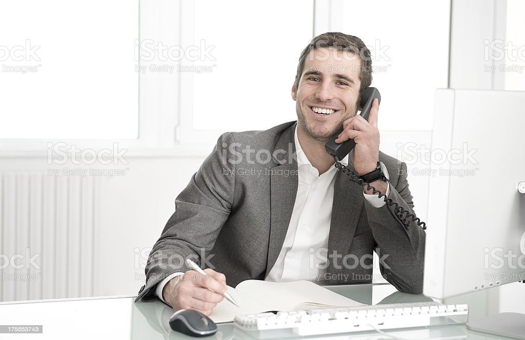 Portrait of young man on the phone Ritratto di giovane al telefono, portrait young business worker computer smile man desk 20-24 Years Stock Photo