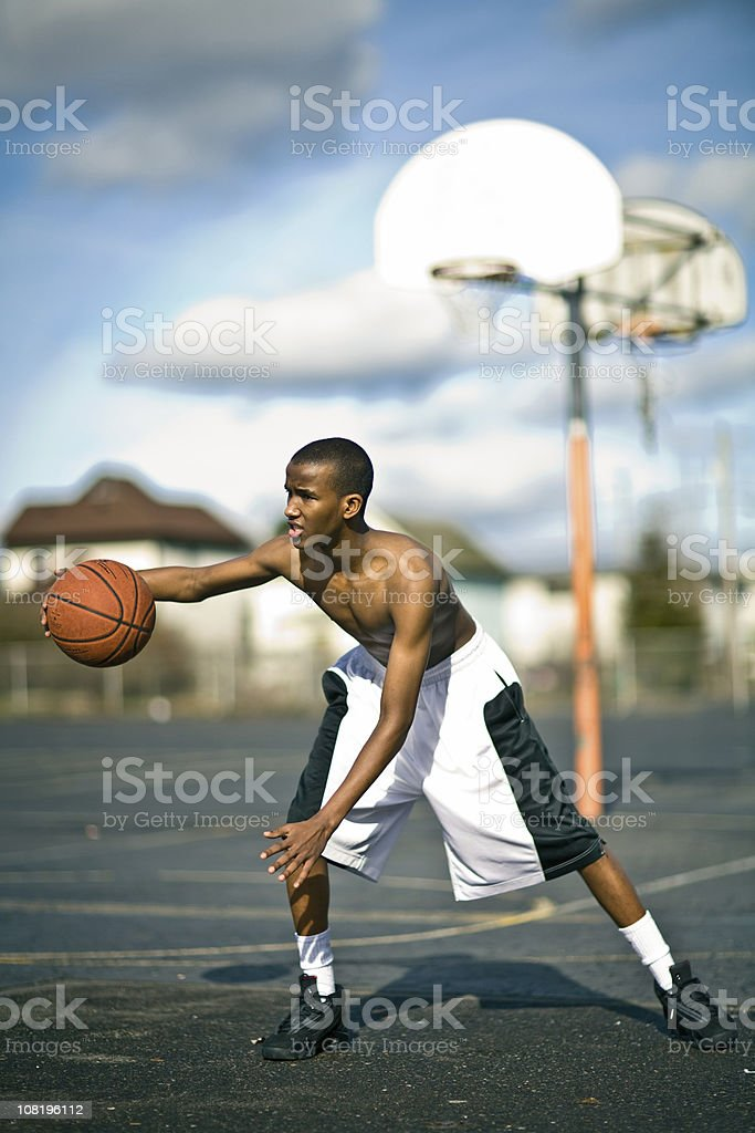 Portrait of Young Man Playing Basketball on Court Outside royalty-free stock photo