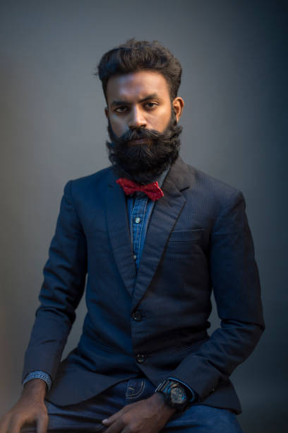 Portrait of young man posing with beard in suit stock photo