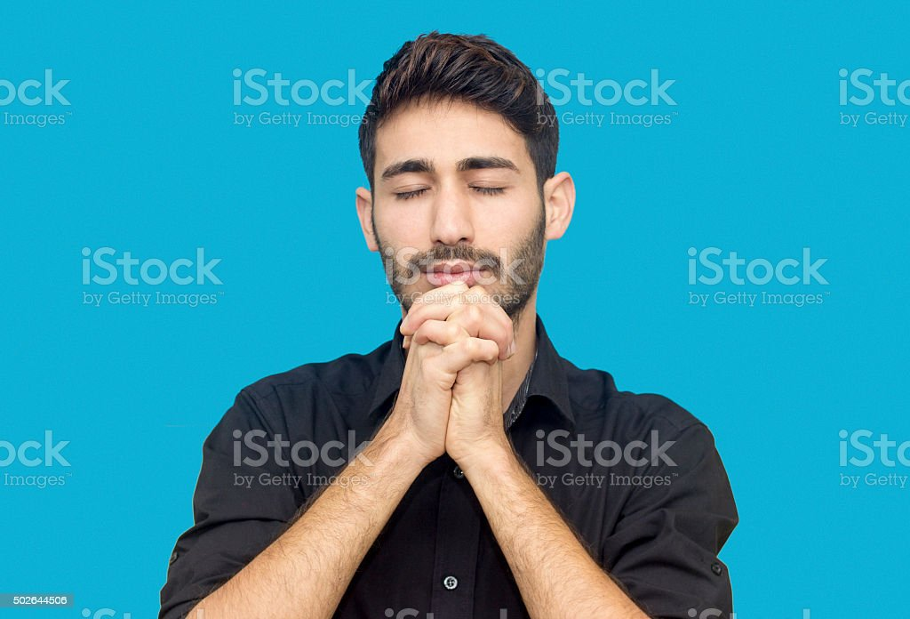 Portrait of young man praying against blue background stock photo