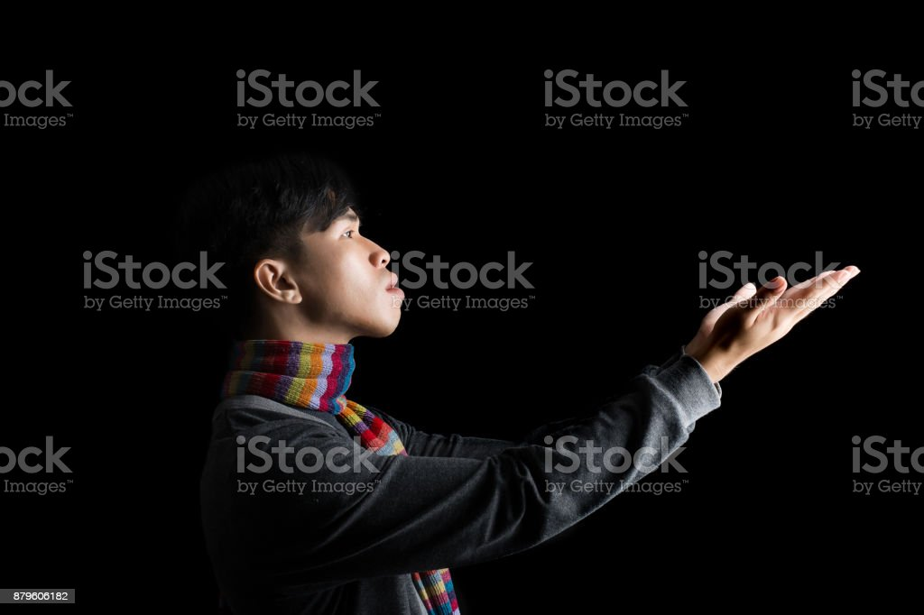 Portrait of young man praying hoping for best asking for miracle isolated black background stock photo