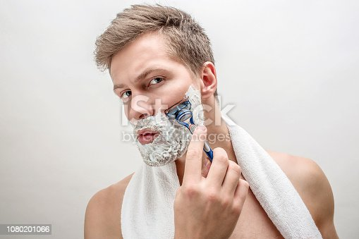 Portrait of young man shaving. He has white foam on beard. Guy is serious and concentrated. Isolated on white background