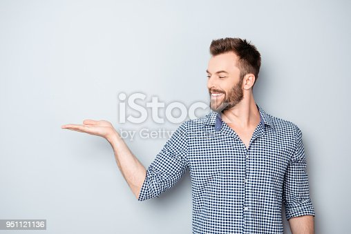 istock Portrait of young man showing product isolated on gray background 951121136