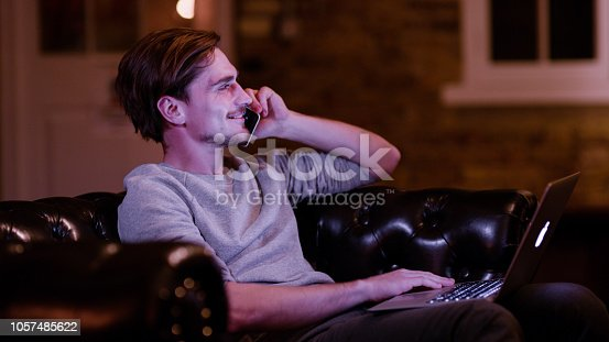 Portrait of young man sitting with laptop on knees and talking on telephone