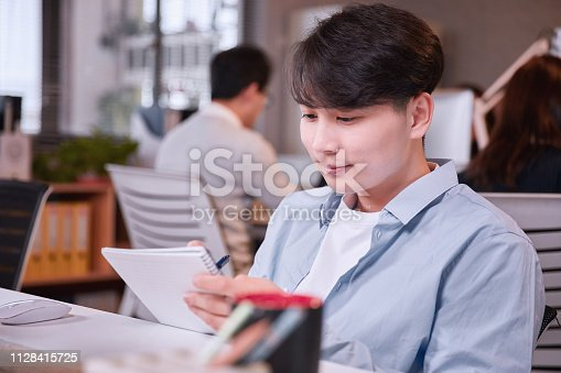 istock Portrait of young man sitting at his desk in the office 1128415725
