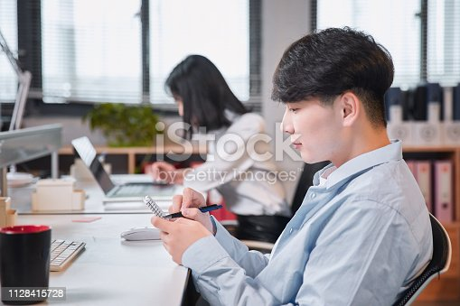istock Portrait of young man sitting at his desk in the office 1128415728