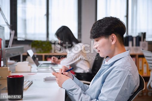 istock Portrait of young man sitting at his desk in the office 1128415732