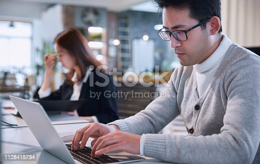istock Portrait of young man sitting at his desk in the office 1128415734