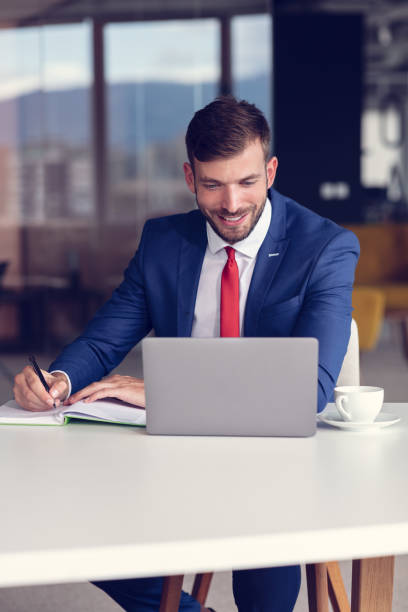 Portrait of young man sitting at his desk in the office stock photo
