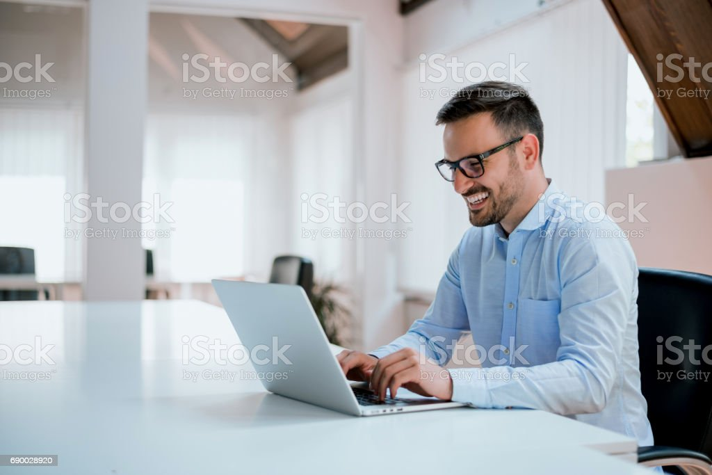 Portrait of young man sitting at his desk in the office royalty-free stock photo
