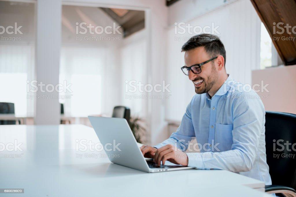 Retrato de jovem homem sentado em sua mesa no escritório foto de stock royalty-free