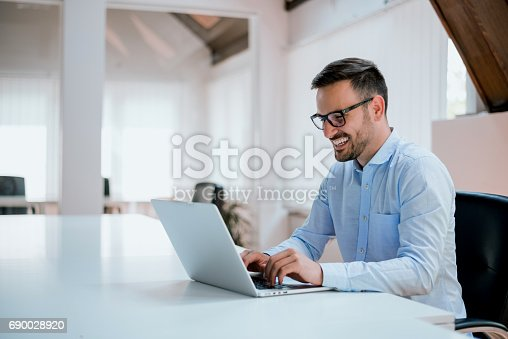 istock Portrait of young man sitting at his desk in the office 690028920