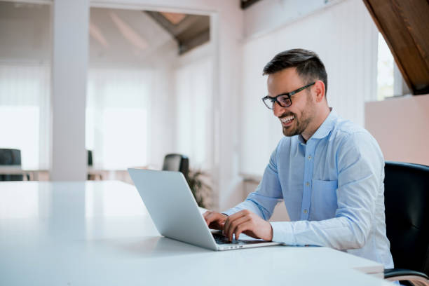 portrait of young man sitting at his desk in the office - laptop stock photos and pictures