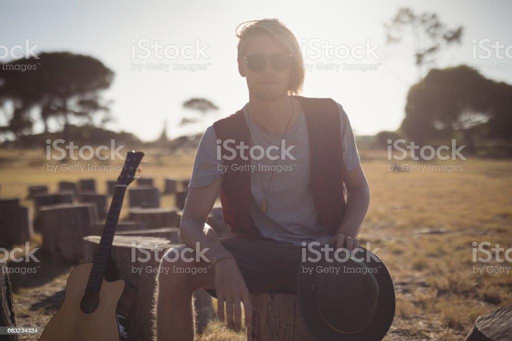 年輕人坐在樹樁上吉他的肖像 免版稅 stock photo