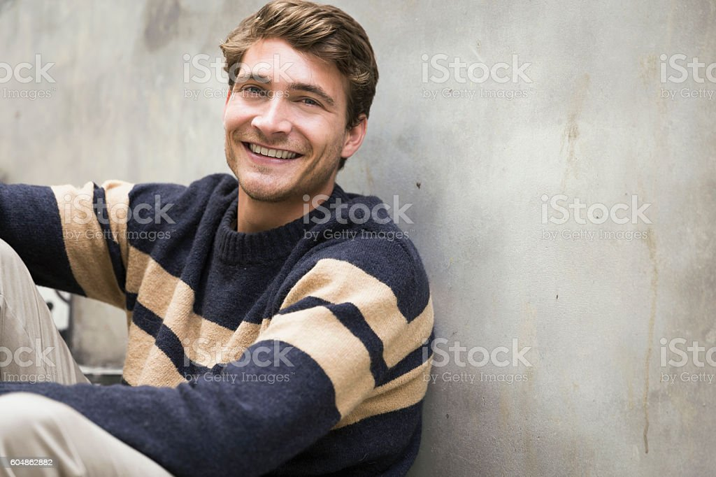 Portrait of young man smiling against wall - foto stock