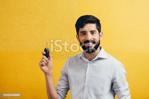 1051147634 istock photo Portrait of young man smiling and holding car keys. Isolated yellow background 1045049062