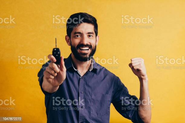 Portrait of young man smiling and holding car keys isolated yellow picture id1047872272?b=1&k=6&m=1047872272&s=612x612&h=xbf81ape8cw1i2l svclcluytvko hp4kveqcd 2obm=