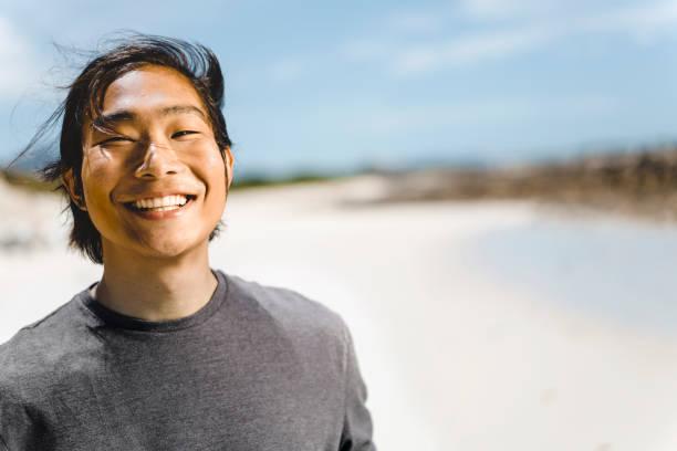 Porträt des jungen Mannes lächelnd am Strand – Foto