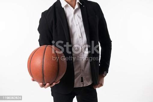 Portrait of young man standing with basketball over white background