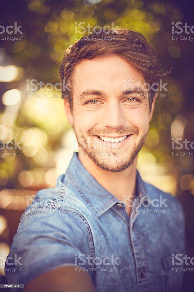 Portrait of young man taking selfie – Foto