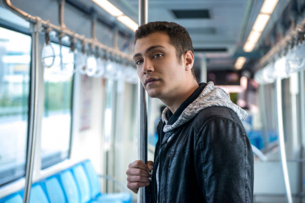 Portrait of young man traveling by subway train looking away stock photo
