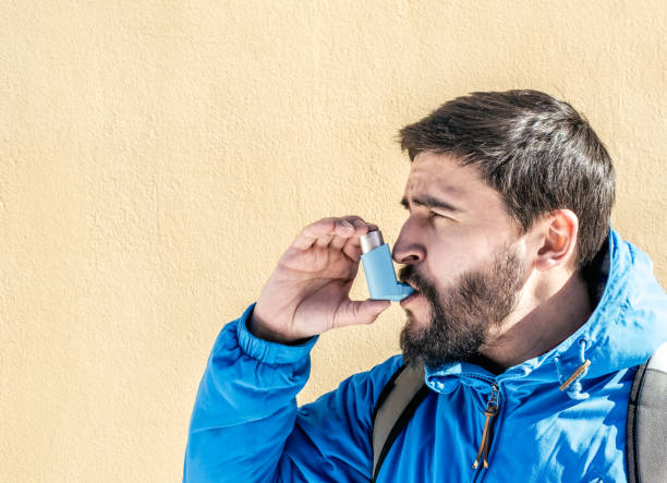 Portrait of young man using asthma inhaler outdoor stock photo