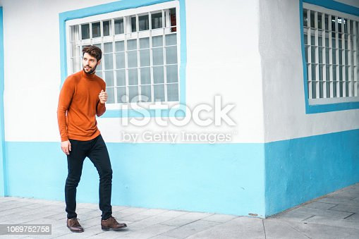 istock Portrait of young man walking. 1069752758