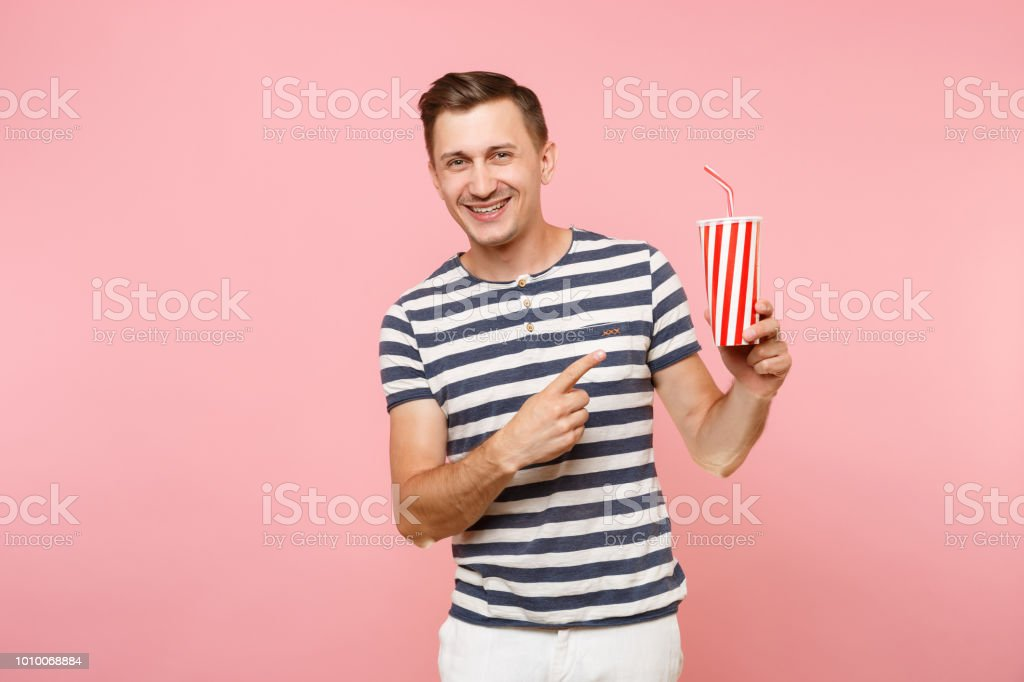 f2526569 Portrait of young man wearing striped t-shirt holding plastic cup of soda,  red