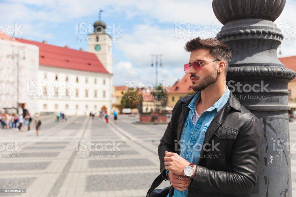 39666e1207 Retrato de hombre joven con gafas de sol apoyado contra el poste de  iluminación foto de
