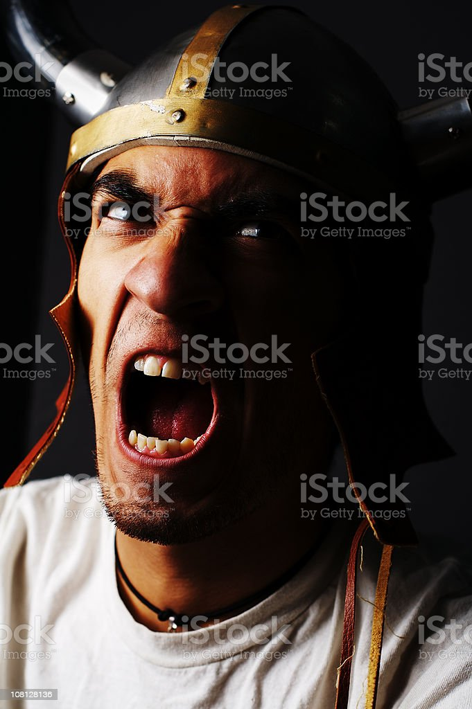 Portrait of Young Man Wearing Viking Hat and Yelling royalty-free stock photo