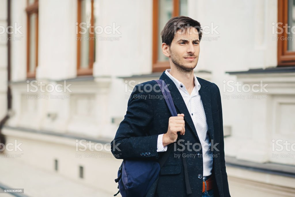 Portrait of young man with backpack in the city stock photo