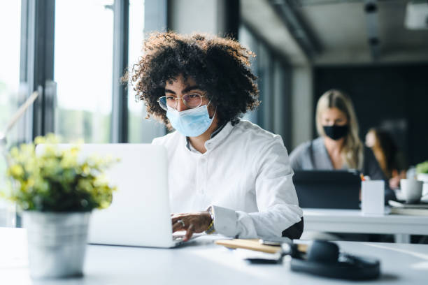 Portrait of young man with face mask back at work in office after lockdown. stock photo