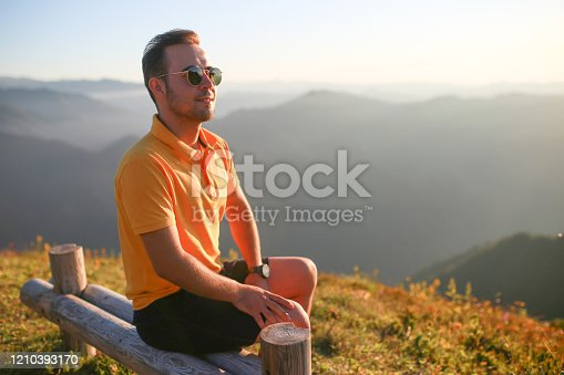 portrait of young man with glasses on summit in sunny weather