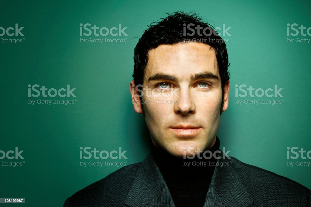 Portrait of Young Man with Green Eyes Against Turquoise Background stock photo