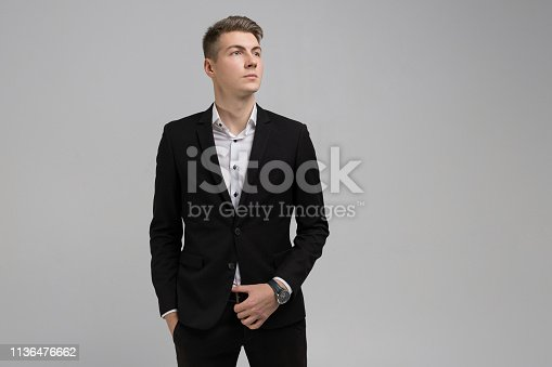 Young businessman full length full length portrait. business young man in an official suit stands alone in bright Studio