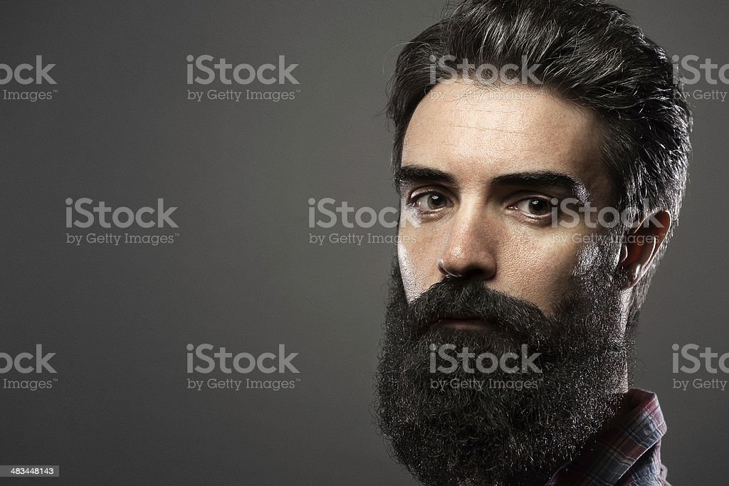 Portrait of young man with long beard on grey background stock photo