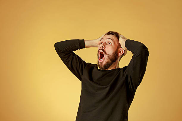 portrait of young man with shocked facial expression - astonishment stock photos and pictures