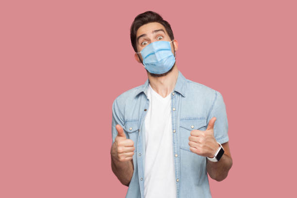 Portrait of young man with surgical medical mask in blue casual style shirt standing, thumbs up and looking at camera with surprised happy face. stock photo