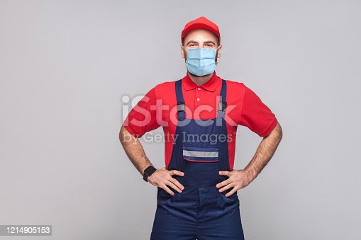 Portrait of young man with surgical medical mask in blue overall, red t-shirt and cap standing and holding hands on waist and looking at camera, indoor, studio shot, isolated on gray background