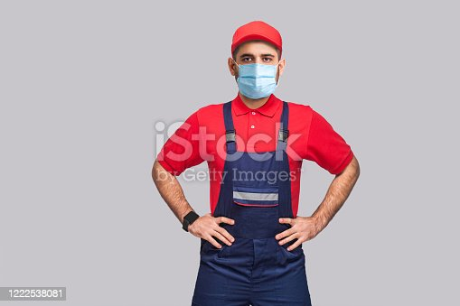 1047558948 istock photo Portrait of young man with surgical medical mask in blue overall, red t-shirt and cap standing and holding hands on waist and looking at camera 1222538081