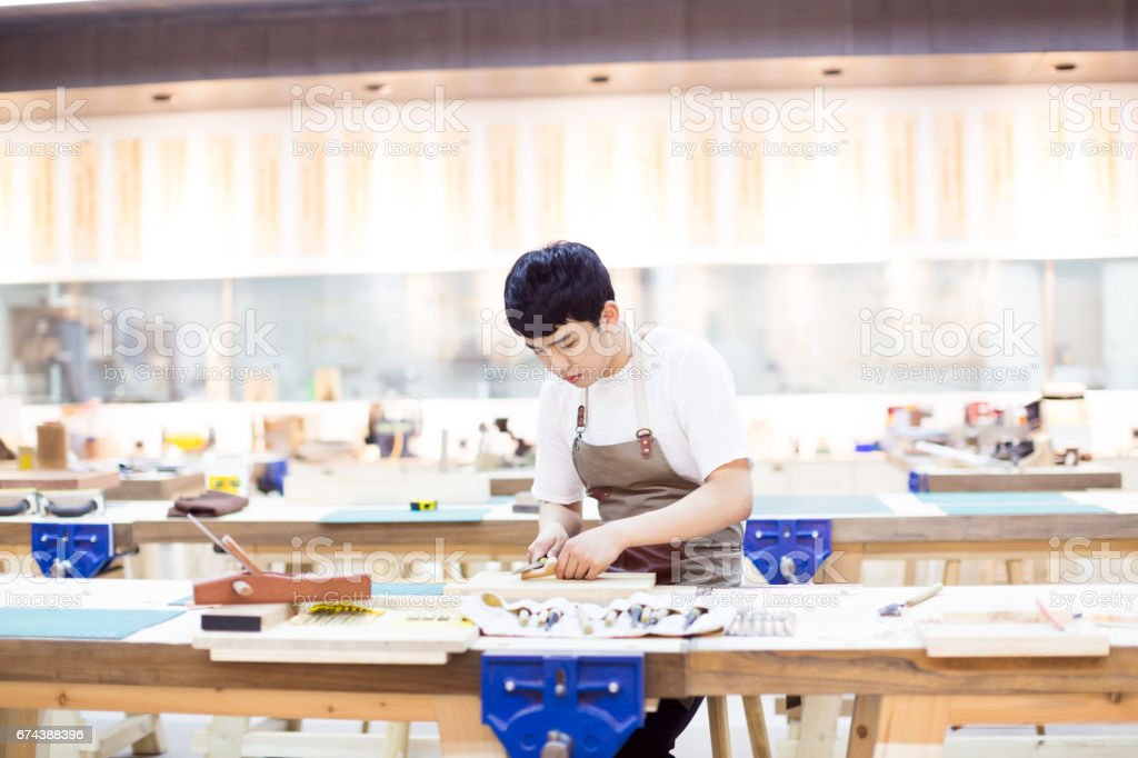 portrait of young man working in a carving workshop stock photo