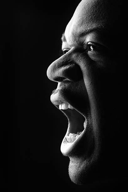 portrait of young man yelling, low key black and white - row of heads stock photos and pictures