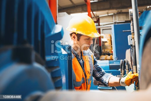 Portrait of a serious worker man with yellow helmet and protective workwear checking pressure device for industry system, opening or closing valve equipment in industrial site factory or utility.