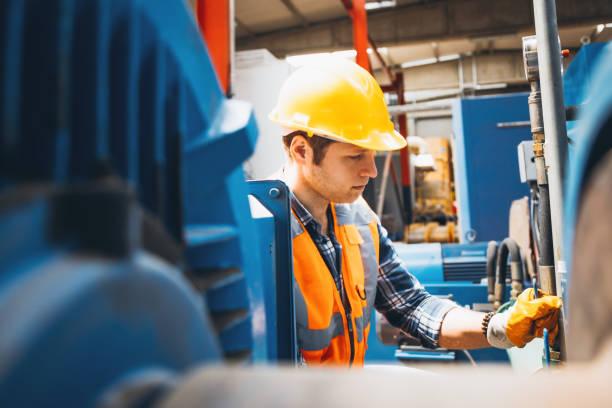 工廠用球閥工作的年輕曼努埃爾工人肖像 - 電子摩打 個照片及圖片檔