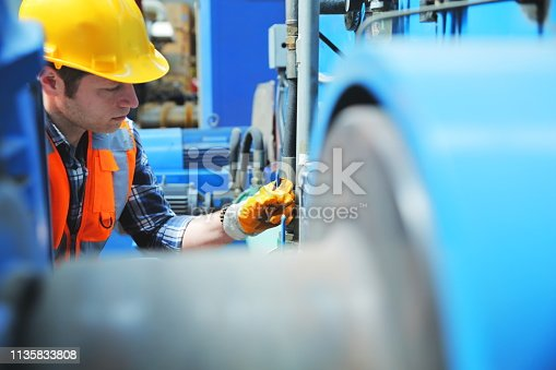 Portrait of young manuel worker man working with ball valves in factory