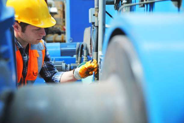 Portrait of young manuel worker man working with ball valves in factory stock photo
