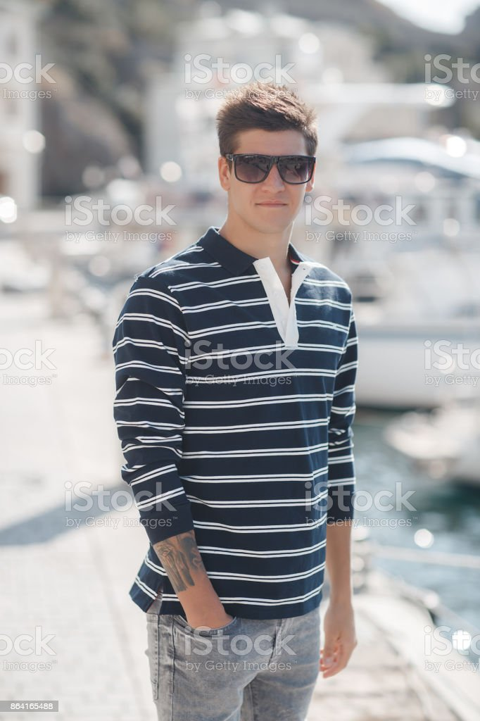 Portrait of young men with luxury yachts in the port. royalty-free stock photo