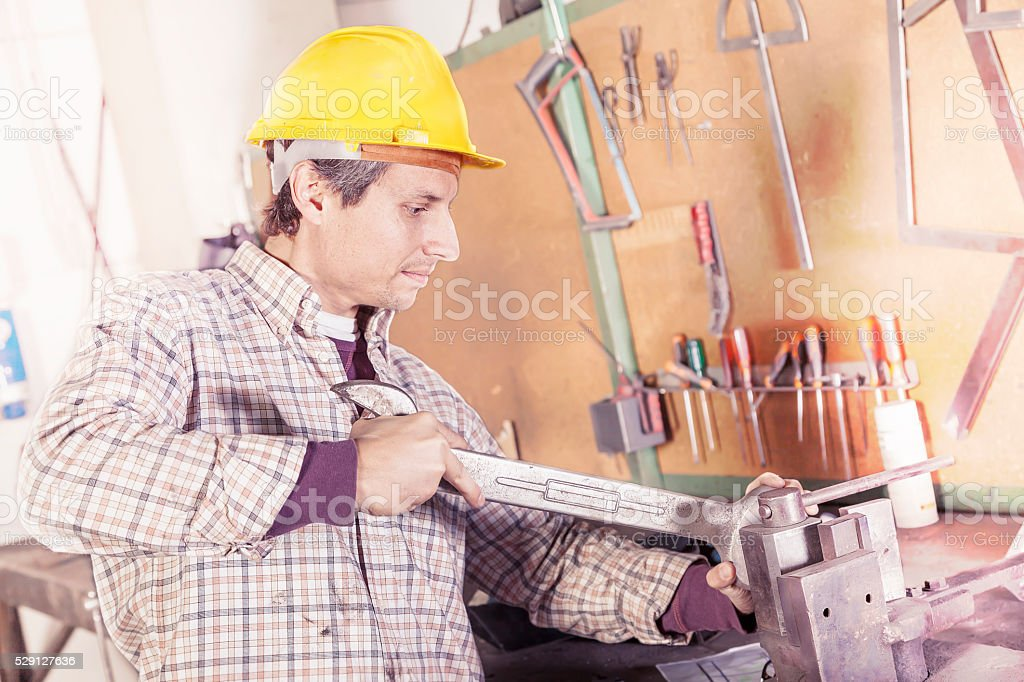 portrait of young metalworker engaged with wrench stock photo