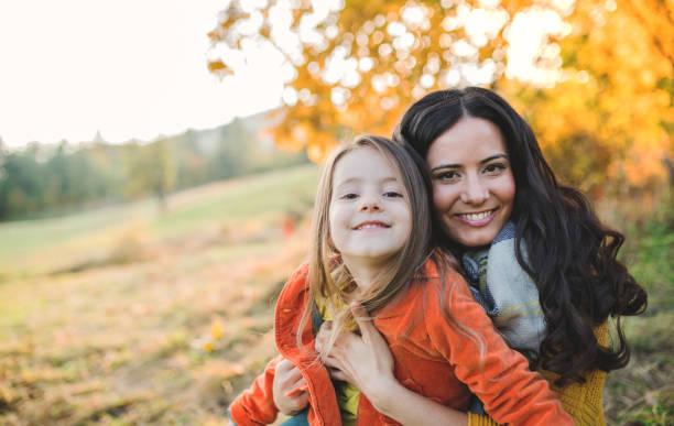 Ein Porträt der jungen Mutter mit einer kleinen Tochter in der Herbstnatur bei Sonnenuntergang. – Foto